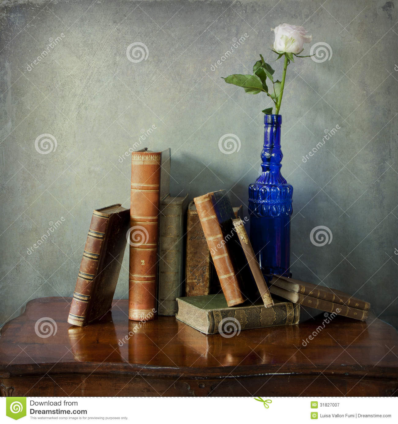 Antique Books And A Pink Rose In Blue Bottle