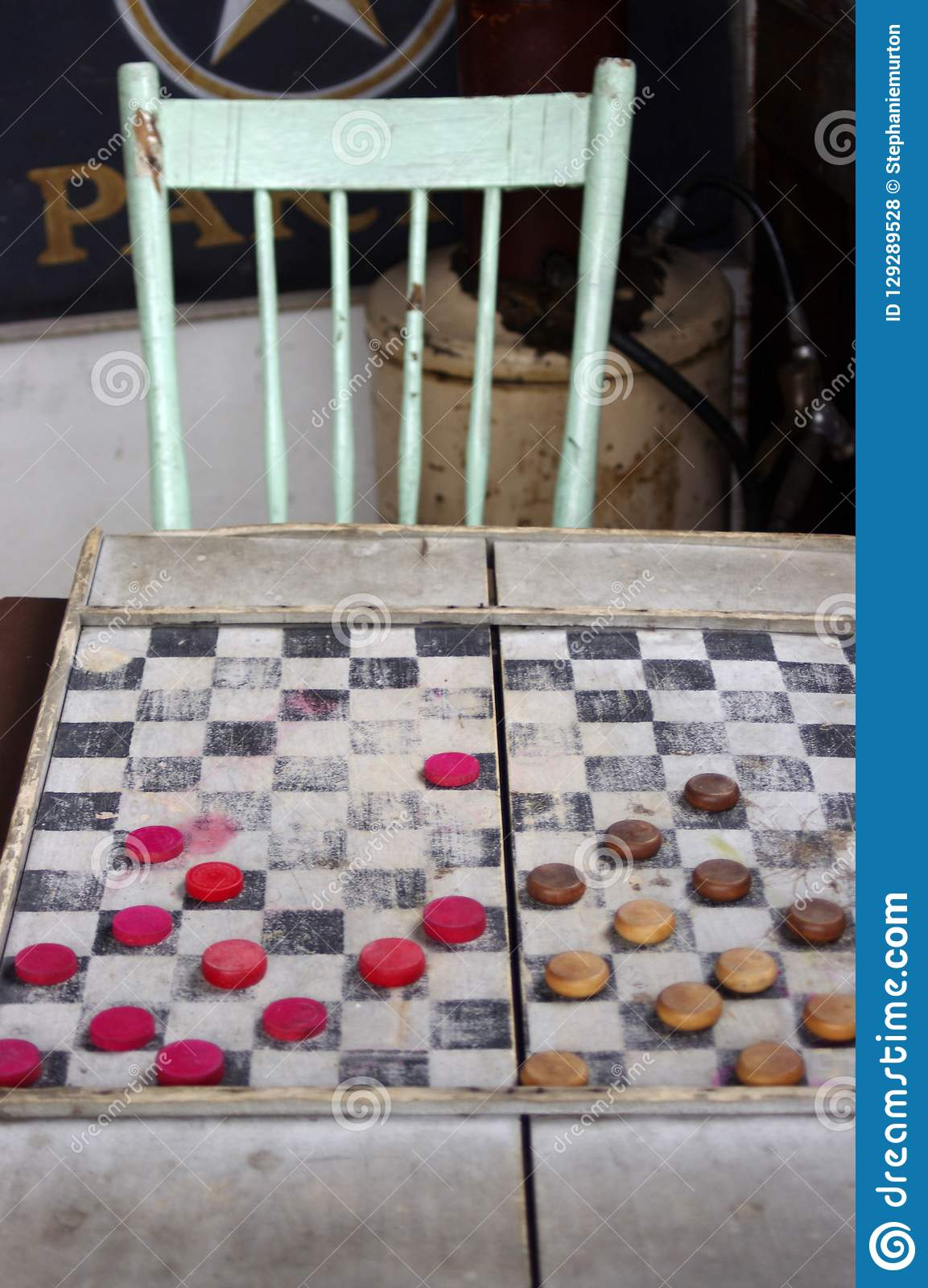 Antique checkers board game with chair in background