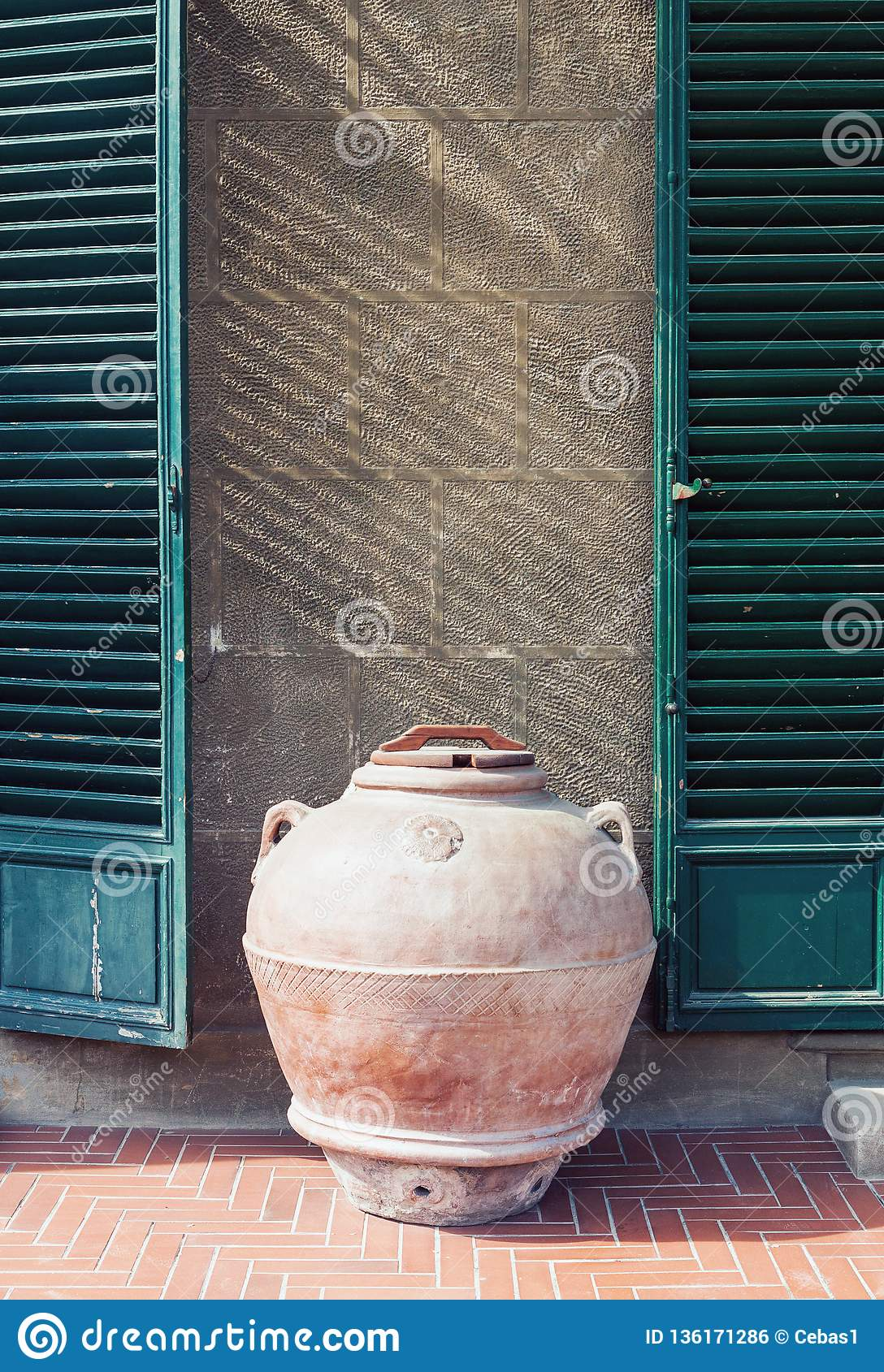 Antique clay jar standing by the wall of an old house in Italy