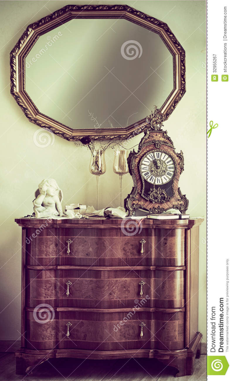 Antique commode with a mantel clock royalty free stock for Antique style wall mirror