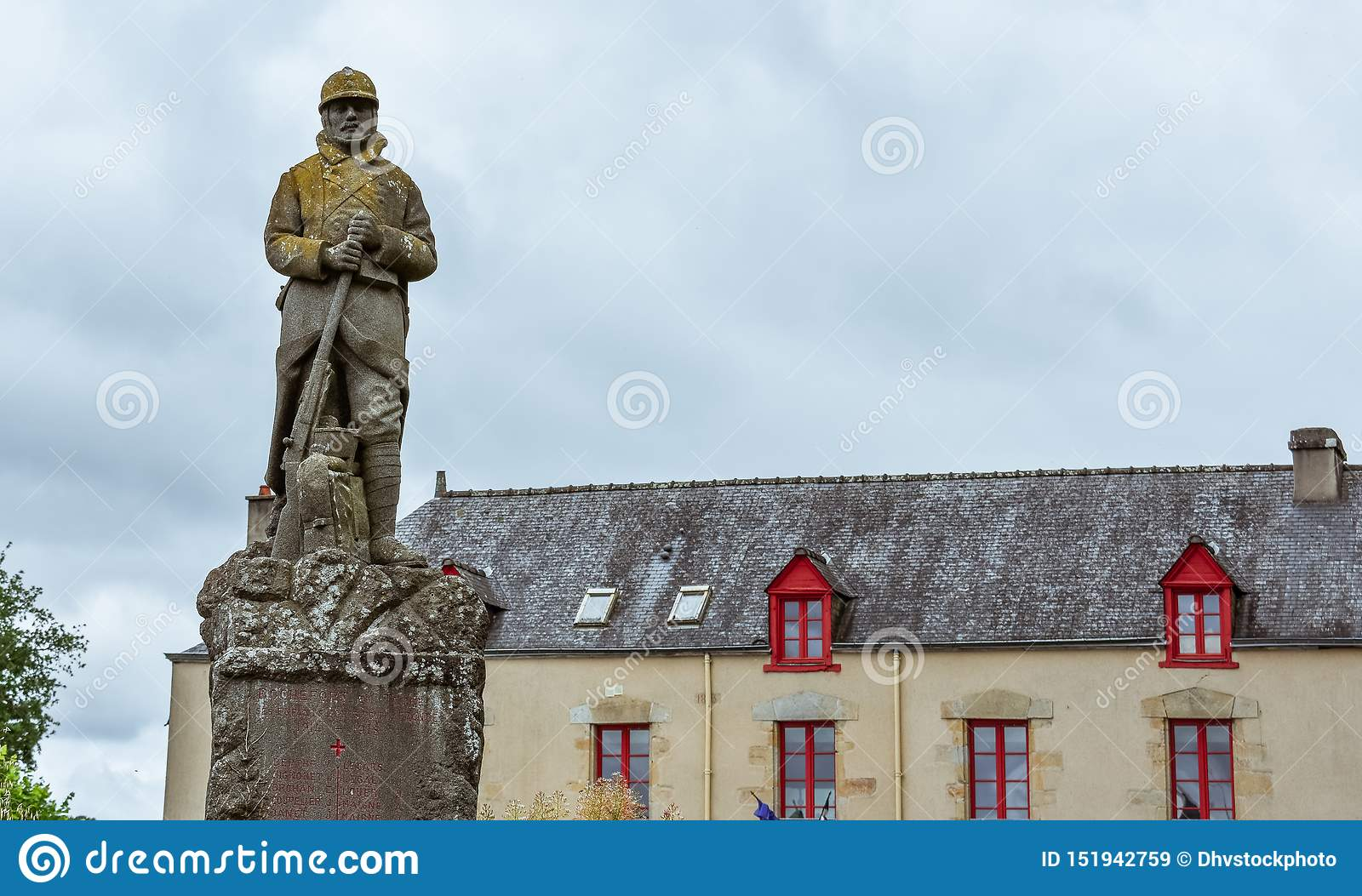 Antique house of the French Brittany and military statue
