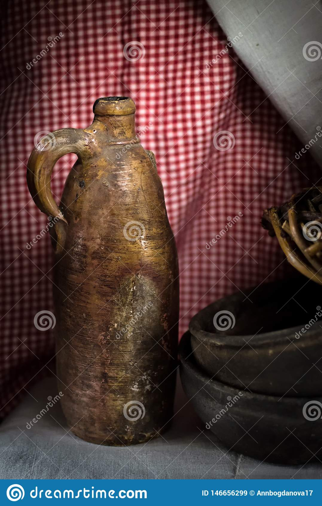 Jug of clay. antique pottery on the background of linen tablecloth