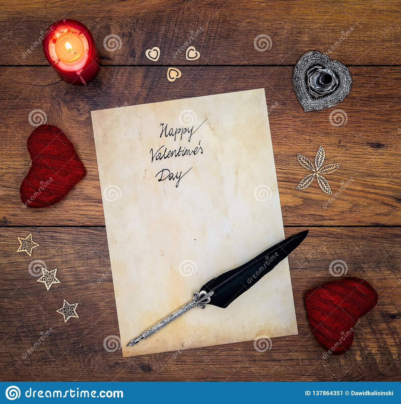 Vintage Valentine`s Day card with red cuddle hearts, wooden decorations, red candle and ink and quill on vintage oak - top view