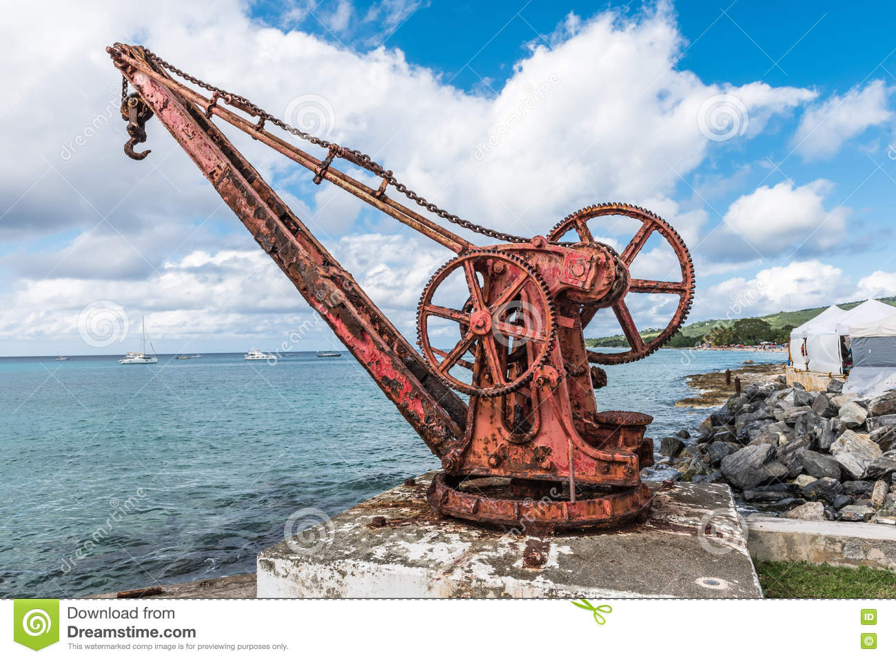 Antique red iron boat crane anchored in concrete along the shore