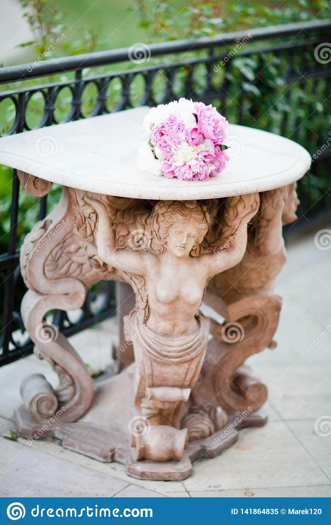 Antique statue supporting a table with wedding bouquet
