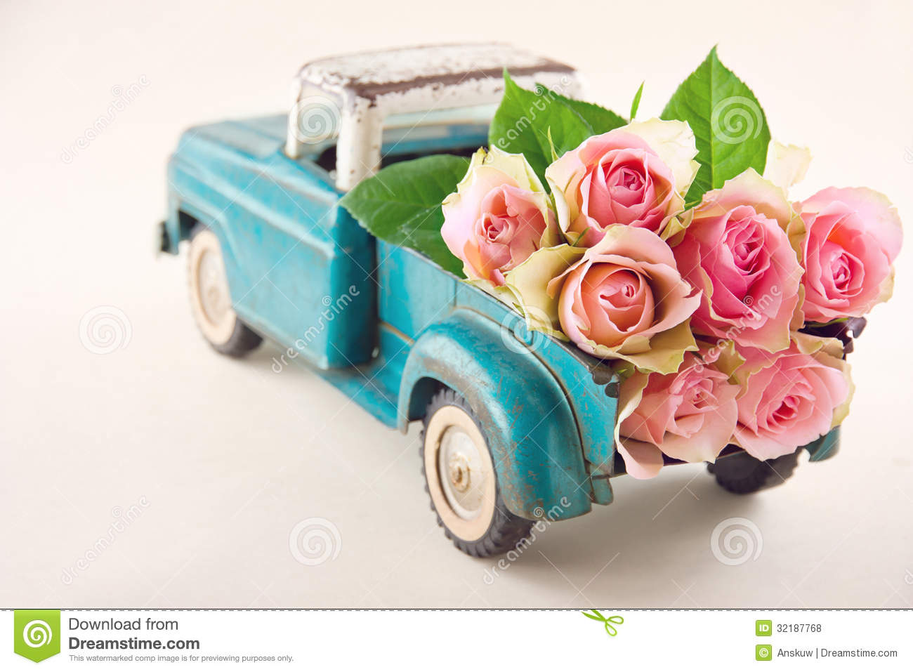 Antique toy truck carrying pink roses