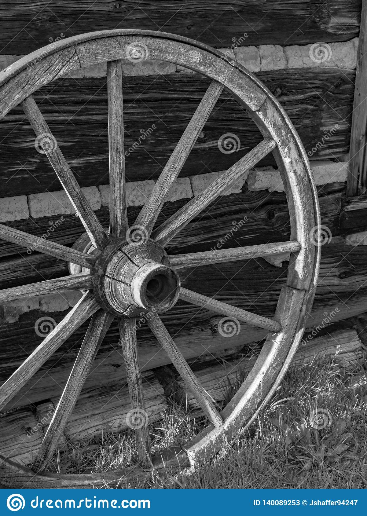 Antique wooden wagon wheel against wooden barn.