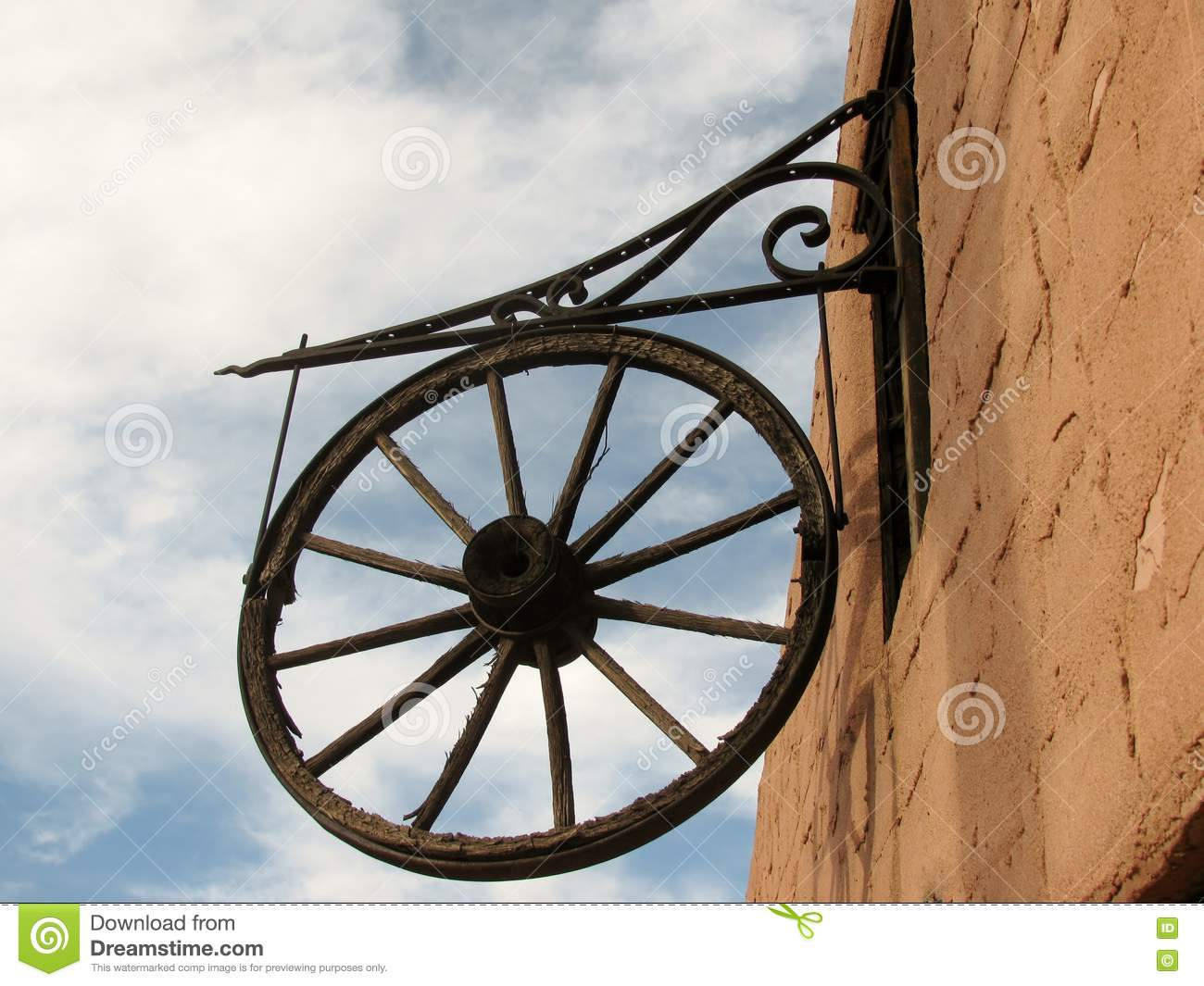 Wagon Wheel Wall Decor antique wooden wagon wheel hanging on a wall as a decoration