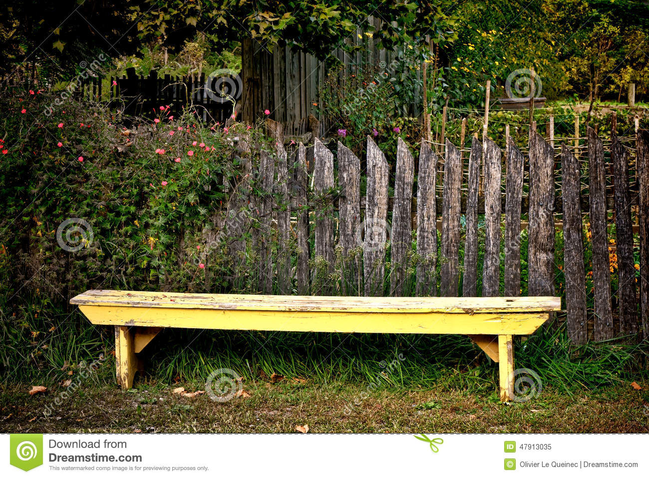 Antique Yellow Garden Bench And Old Vintage Fence Stock