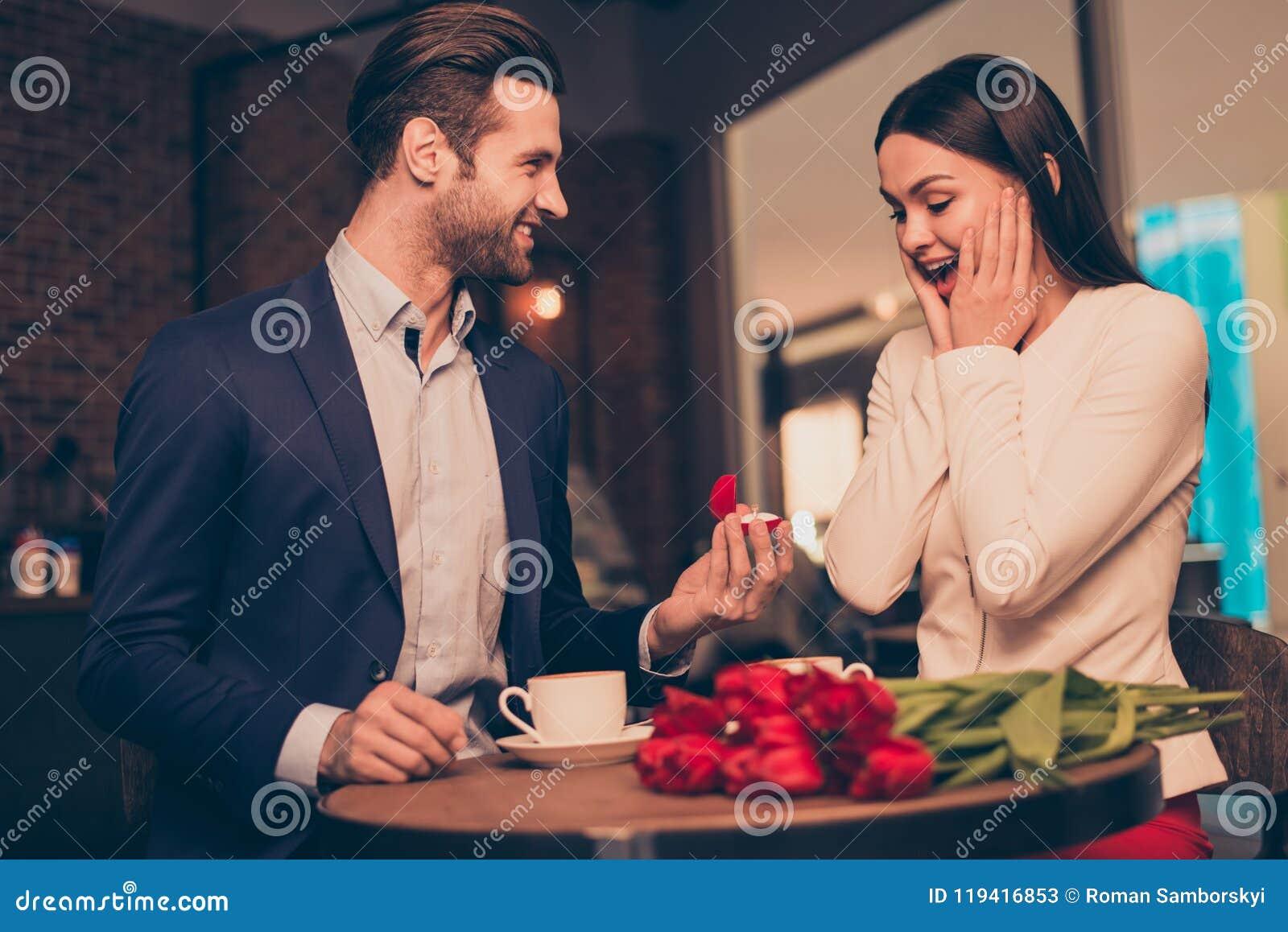 Antrag in einem Café mit unerwartetem Schmuck des Ringes und der Momentflitterwochen machend der Blumen, schellen Sie Konzept-Fra