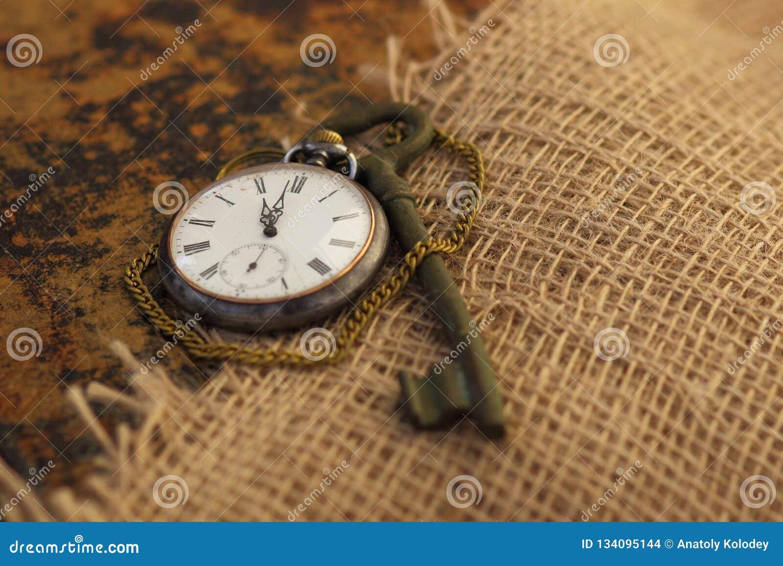 Antyczny kieszeniowy zegarek i klucz na starym folio zakrywającym z starym parciakiem koncepcja przechodzącego razem Wiedzy wiecz