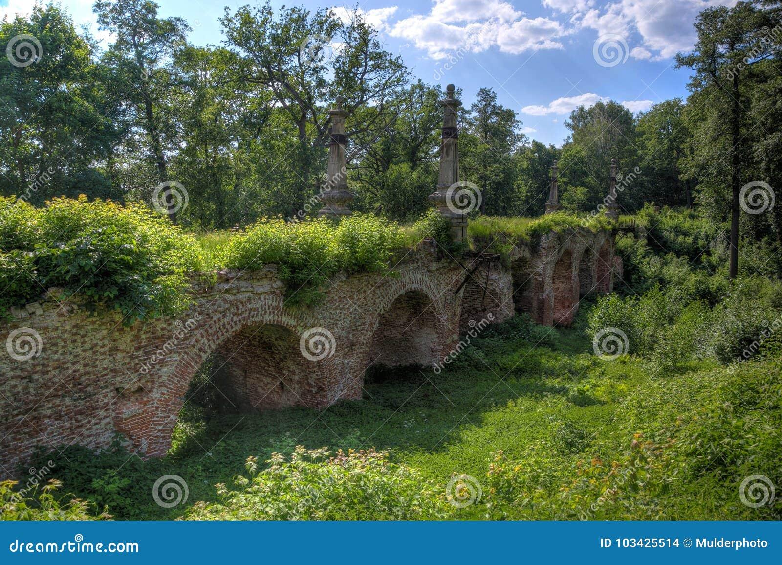 Antyczny rujnujący przerastający czerwonej cegły most w lesie
