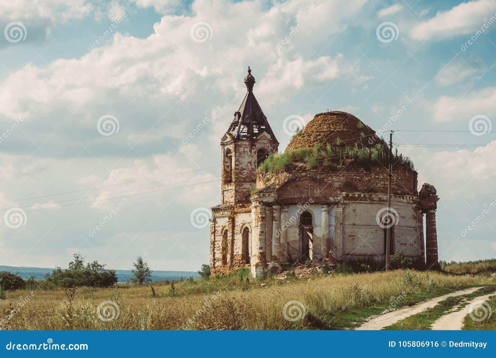 Antyczny rujnujący Rosyjski kościół lub świątynia przerastający z trawą wśród pola