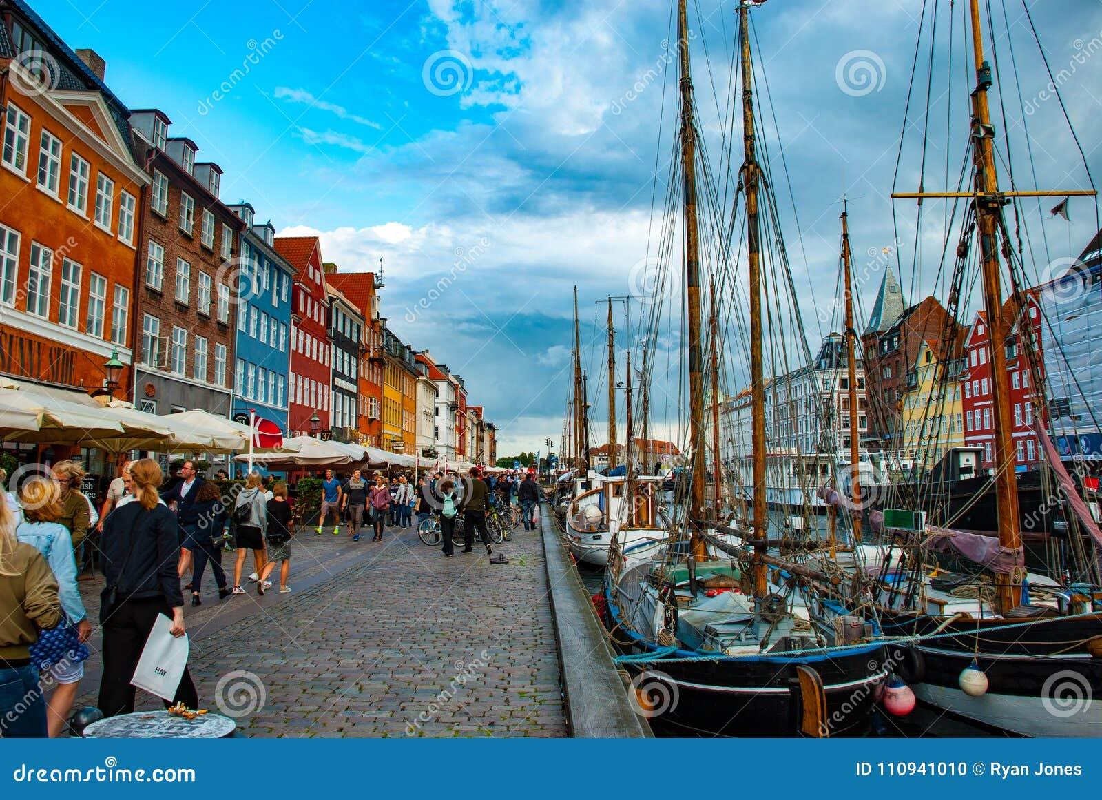 Antyków statki w Nyhavn, Kopenhaga, DK podczas gdy turyści podziwiają okręgu