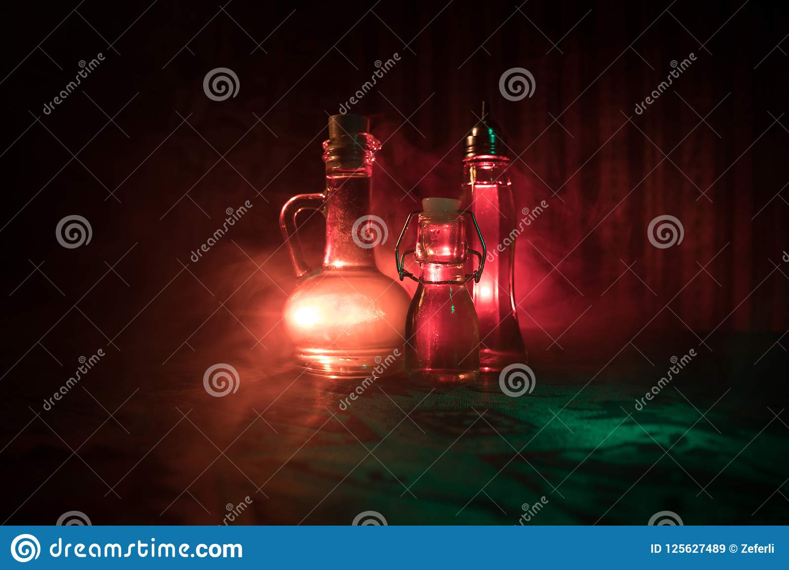 Antyka i rocznika szklana butelka na ciemnym mgłowym tle z światłem Jad lub magia ciecza pojęcie