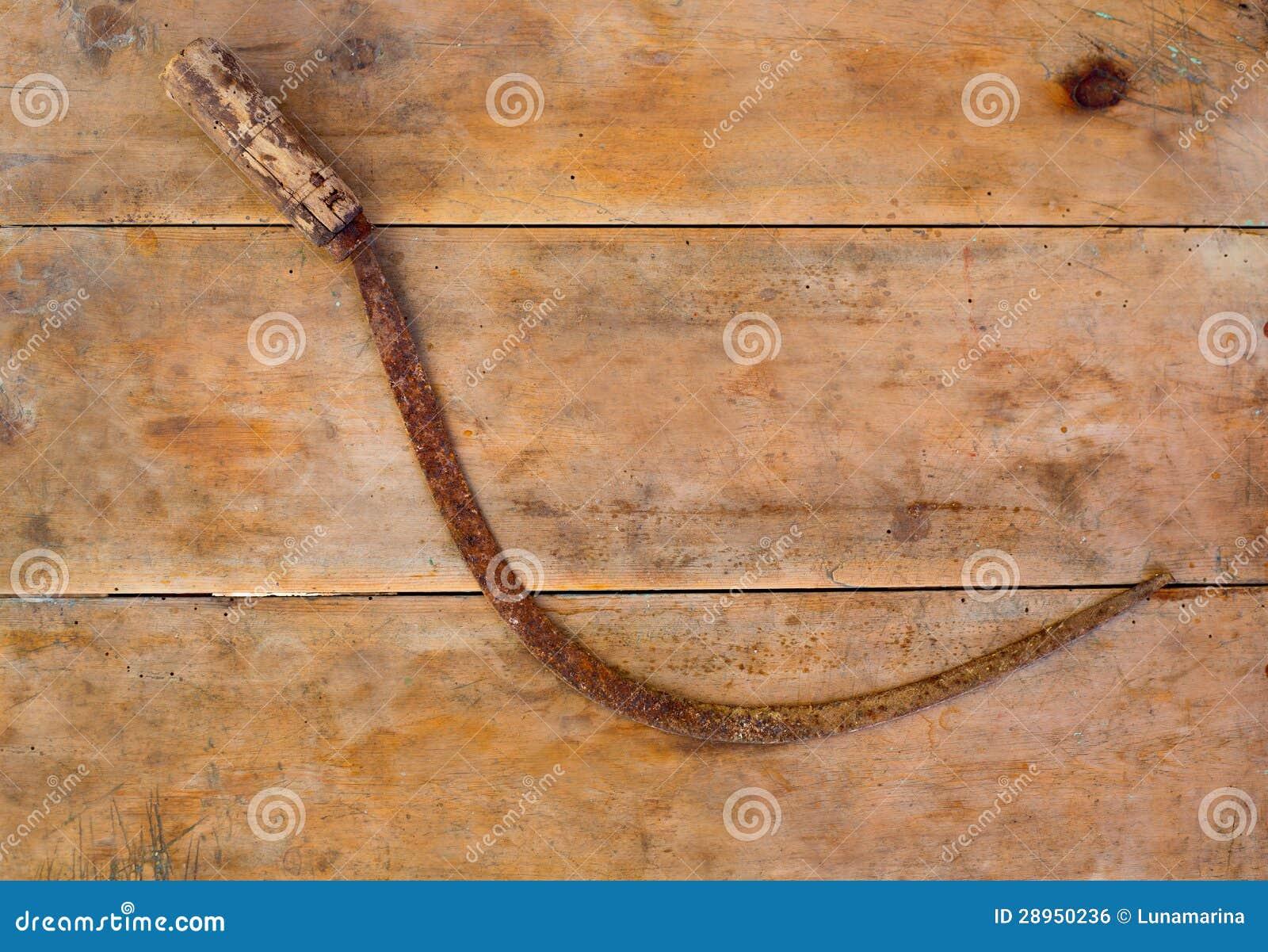 Antykwarski sierpa handtool rdzewiał na starzejącym się rocznika drewnie