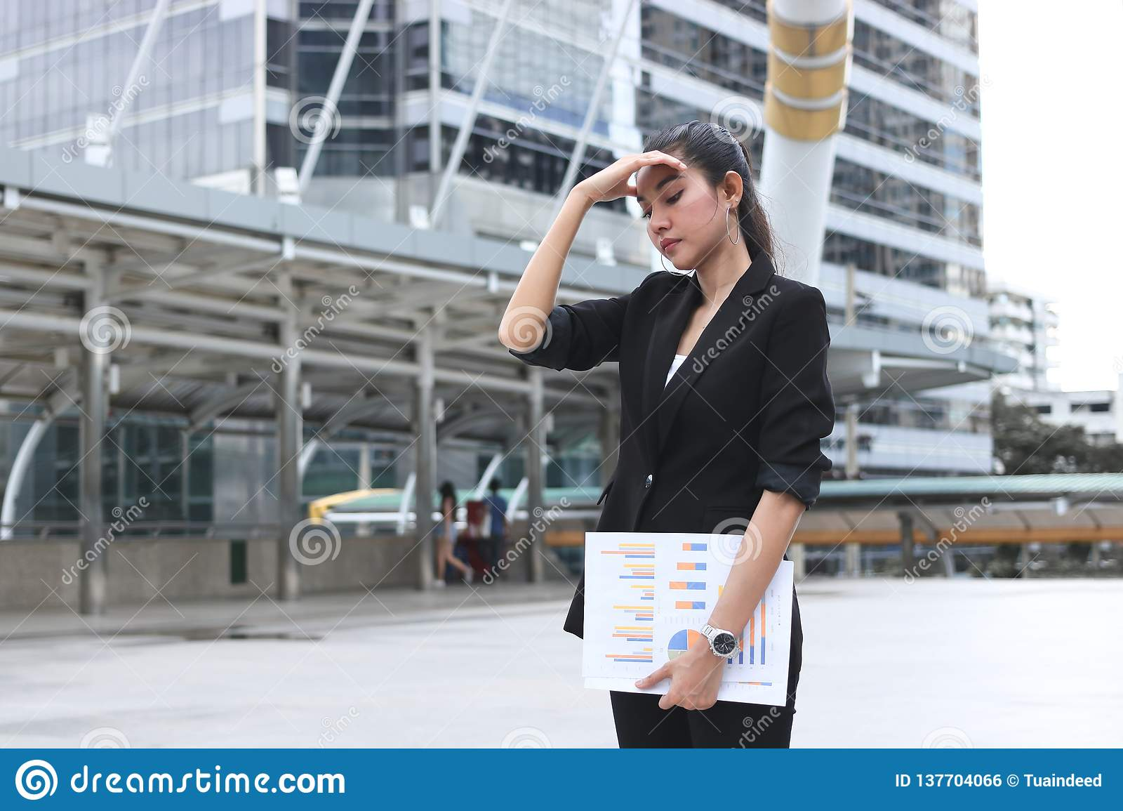 Anxiety stressed young Asian business woman in depression outdoors