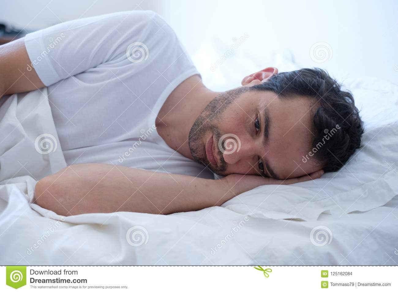 Anxious Man Lying In His Bed And Feeling Bad Stock Photo