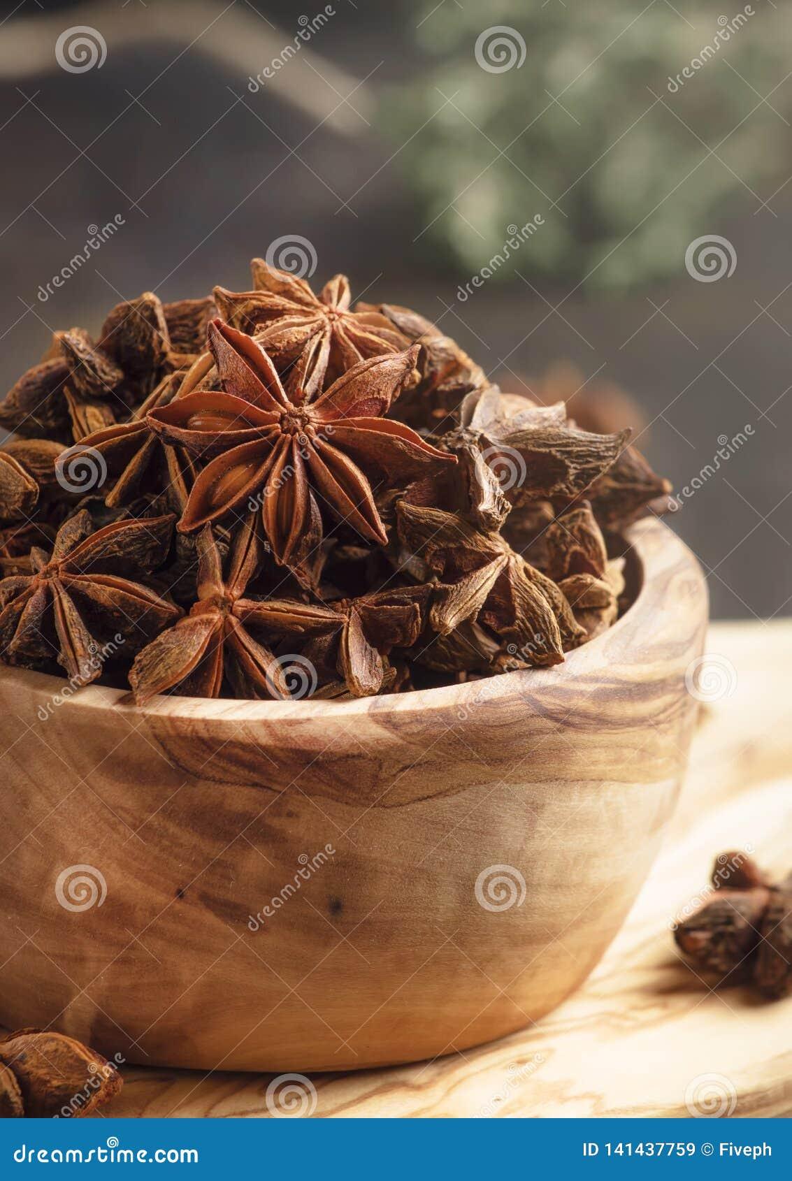 Anyż gra główna rolę w drewnianym pucharze, ciemny kuchennego stołu tło, selekcyjna ostrość