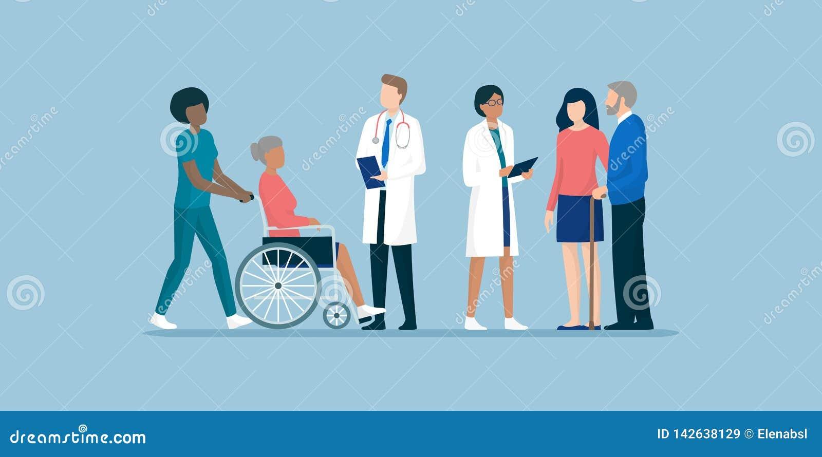 Anziani con il gruppo dei badante e di medici professionisti