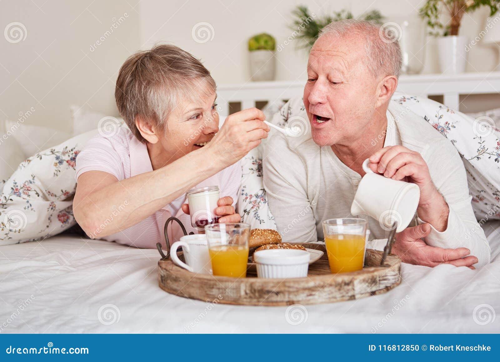 Anziani felici che mangiano prima colazione a letto