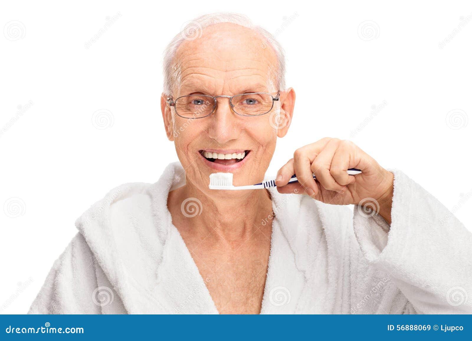 Anziano allegro che pulisce i suoi denti