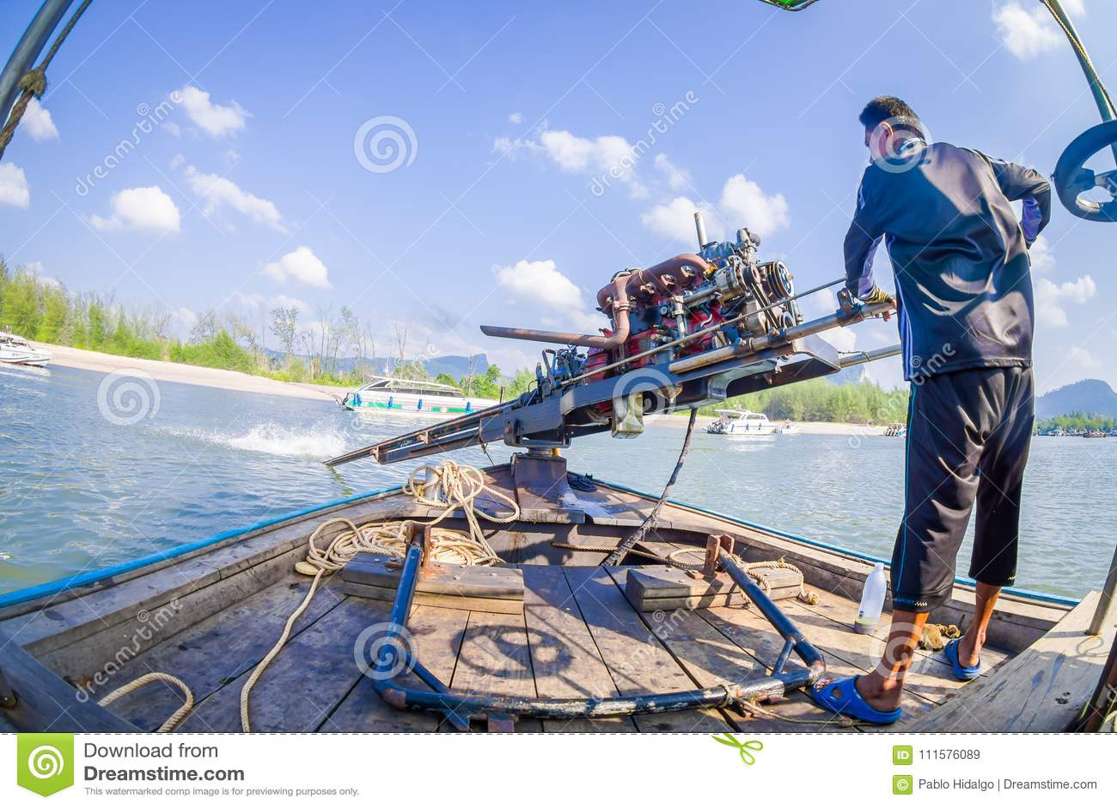 AO NANG TAJLANDIA, LUTY, - 09, 2018: Zakończenie up niezidentyfikowany mężczyzna manipuluje łódkowatego silnika z zamazaną naturą
