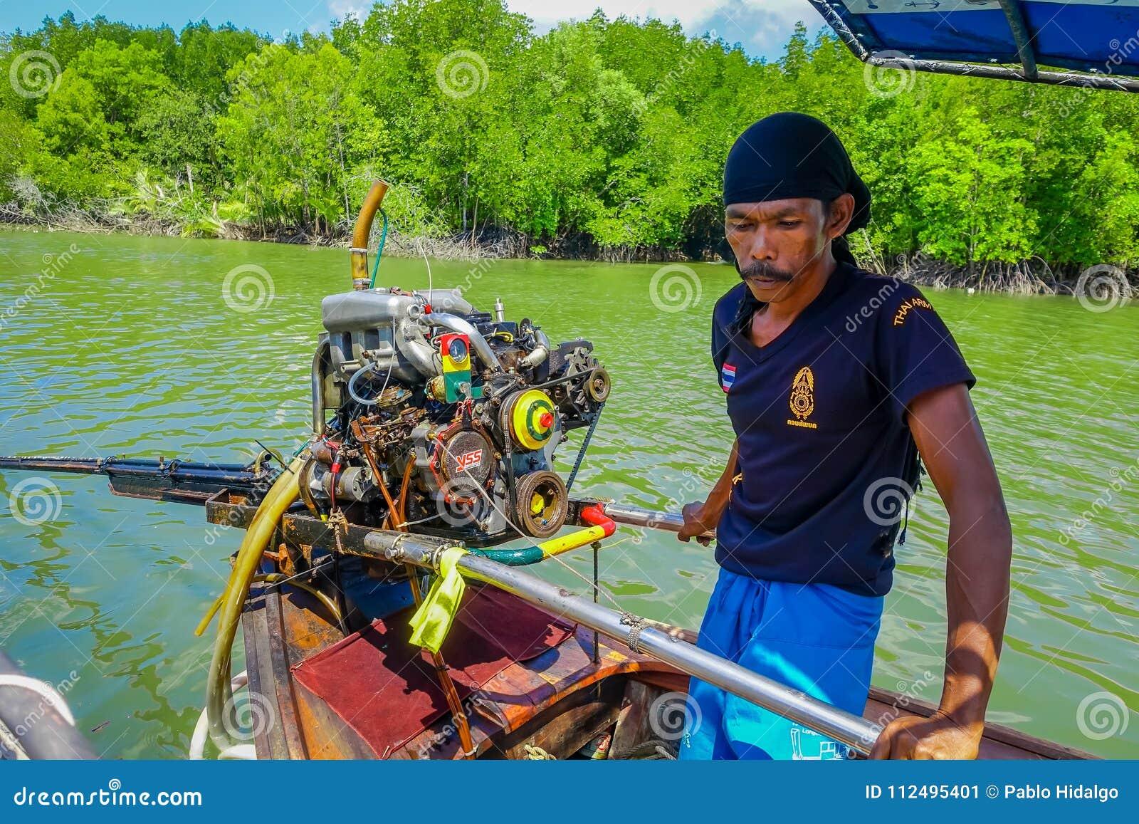 AO NANG, THAILAND - FEBRUARI 09, 2018: Oidentifierad man som behandlar en fartygmotor av det långa fisihngfartyget med en natur