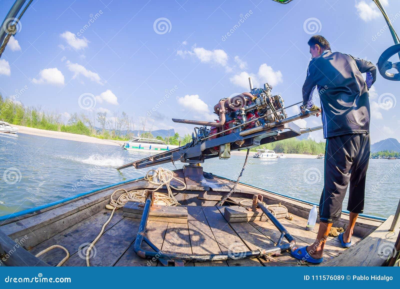 AO NANG, THAILAND - FEBRUARI 09, 2018: Slut upp av den oidentifierade mannen som behandlar en fartygmotor med en suddig natur