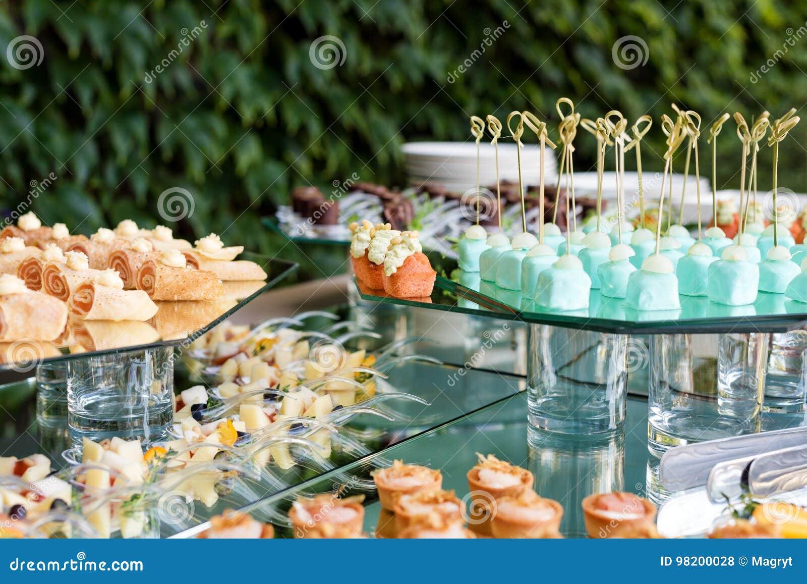 Apéritifs, repas sur le pouce, nourriture de partie, glisseurs Canape, tapas Table servie au café de terrasse d été Service de re