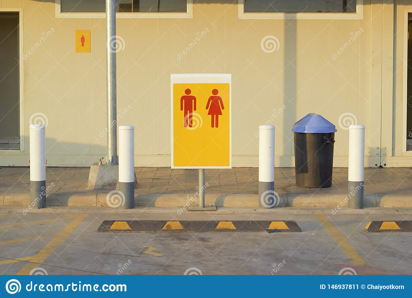 Aparcamiento delante del cuarto de baño en la gasolinera, muestras, mujeres, fondo amarillo rojo de los hombres Iconos del hombre
