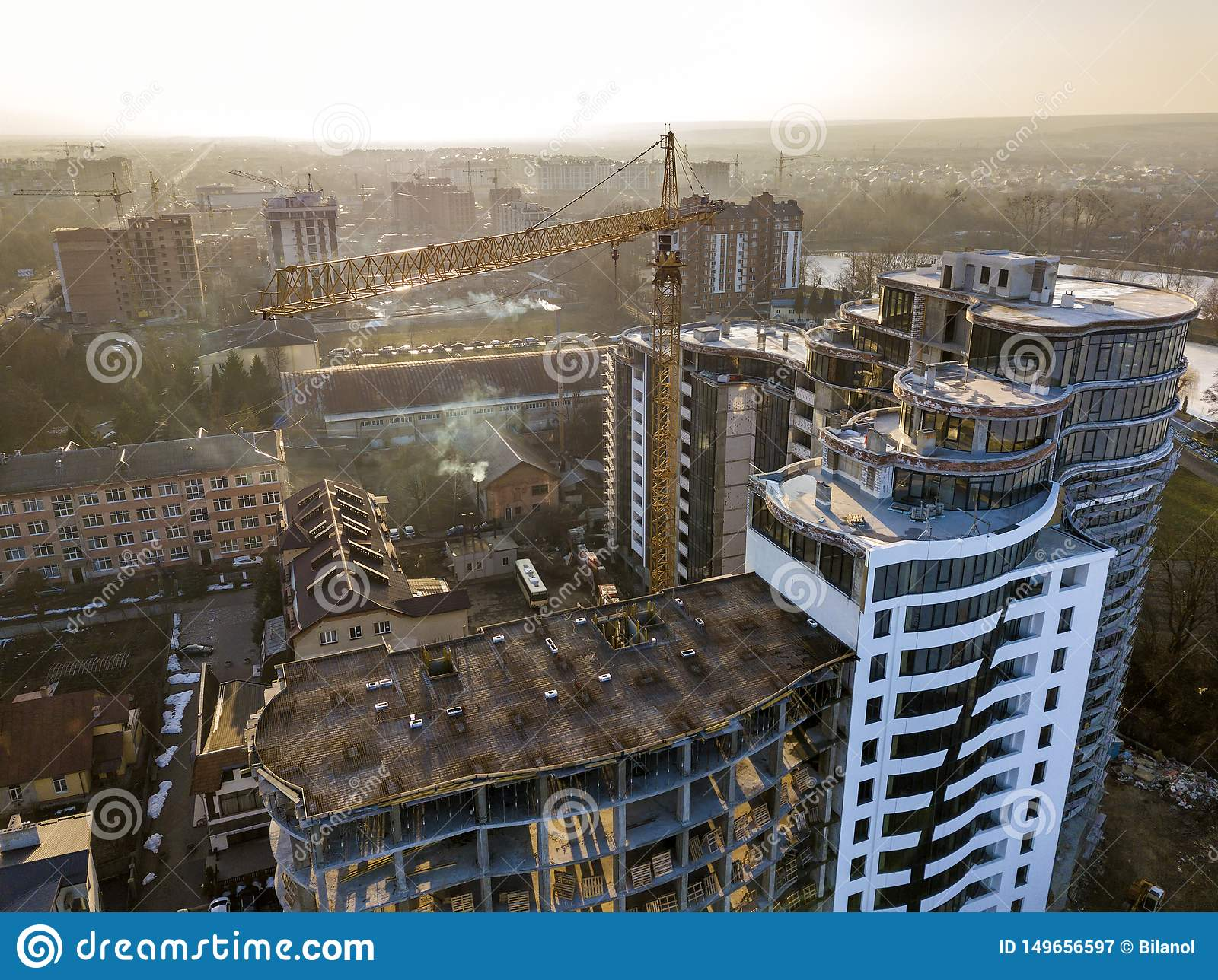 Apartment or office tall building under construction, top view. Tower crane and city landscape stretching to horizon. Drone aerial