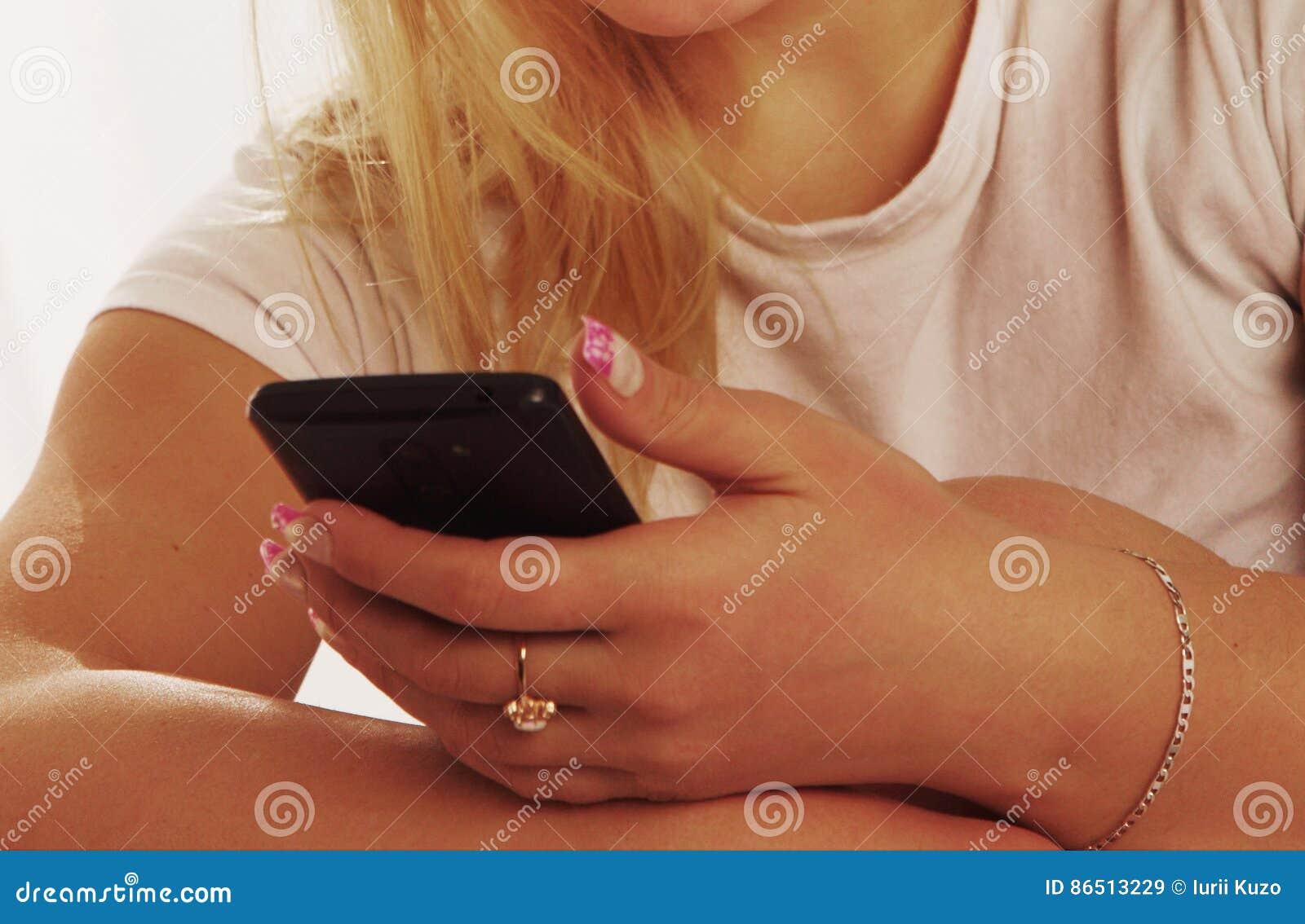 Apego social dos meios mulher bonita nova que guarda um smartpho