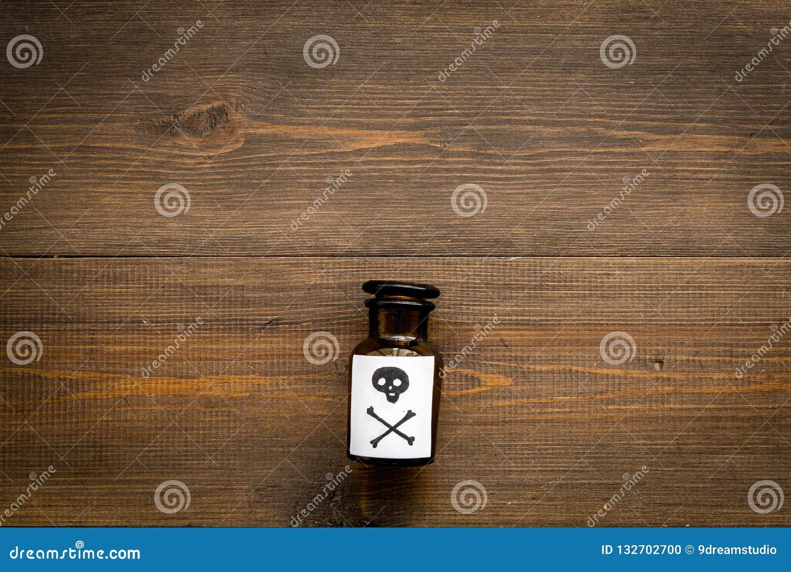 Apegos peligrosos, entretenimiento peligroso veneno Botella con el cráneo y la bandera pirata en el top de madera oscuro del fond