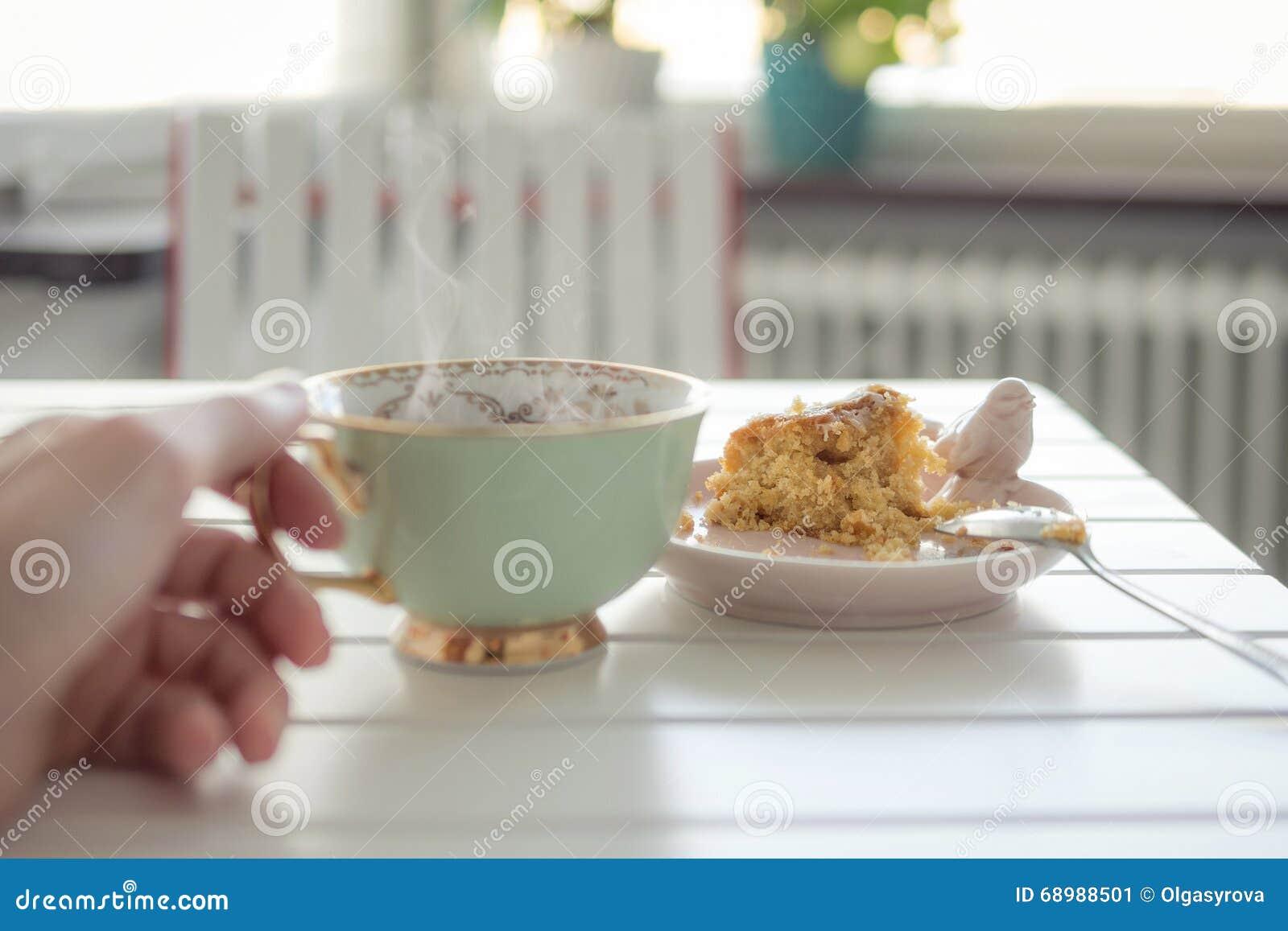 Apelmácese y la mano que sostiene una taza de té