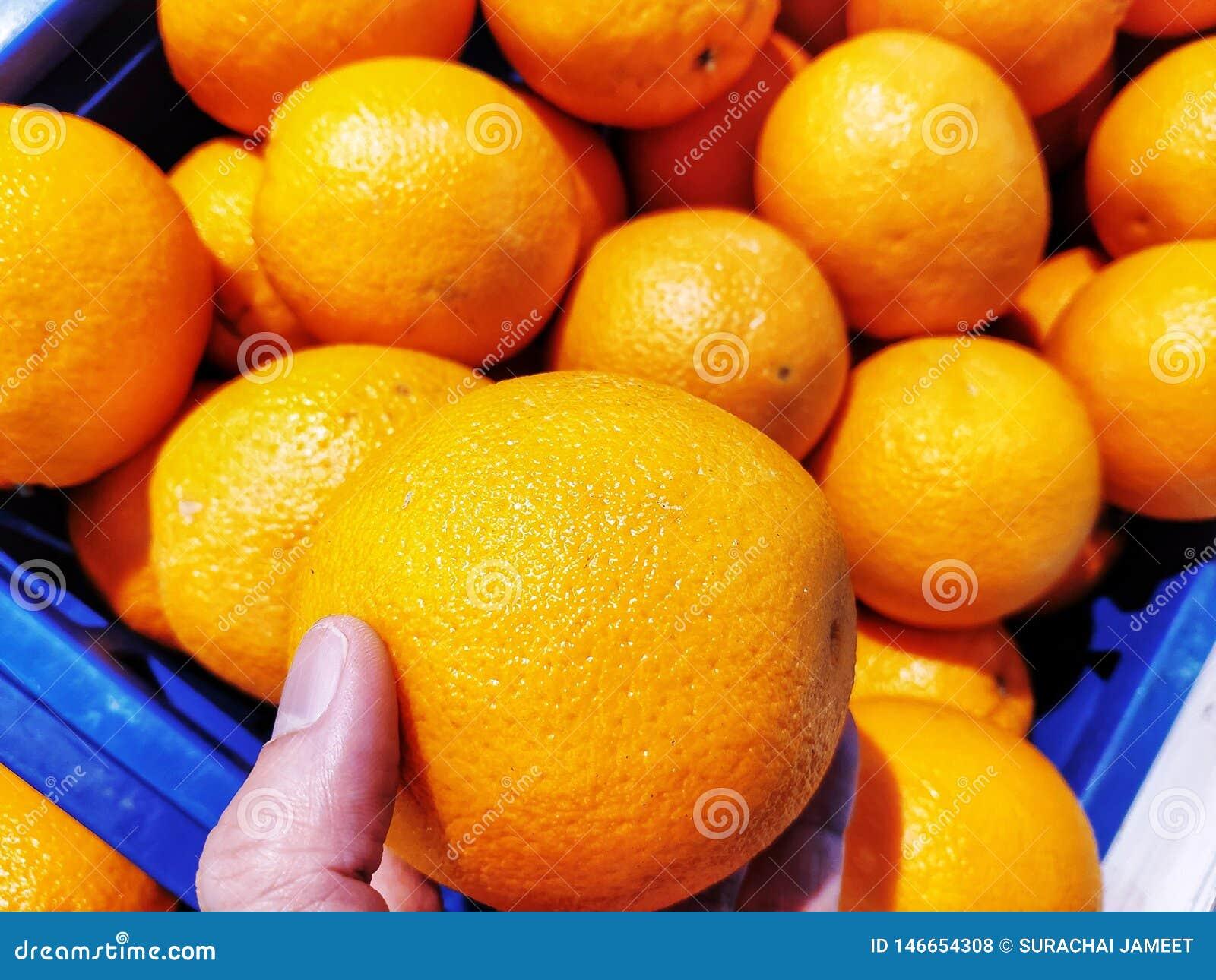 Apelsinen är i en hand Många är mer bak platserna i en blå korg