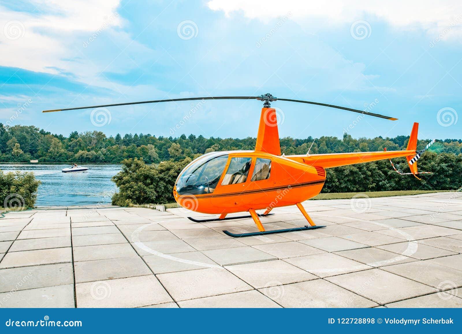 Apelsinen färgade helikoptern som parkerades på en konkret tjock skiva under blåa himlar