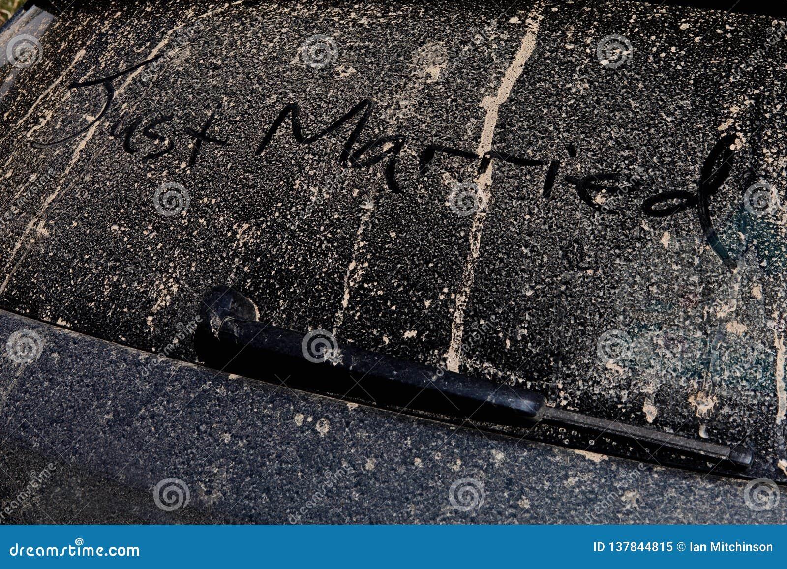 Apenas casado trazado a mano en la parte de atrás de un coche fangoso en un sol