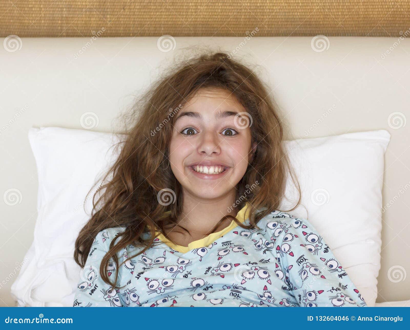 Apenas muchacha bonita despierta del adolescente con la cara divertida de la emoción y el pelo salvaje en la cama