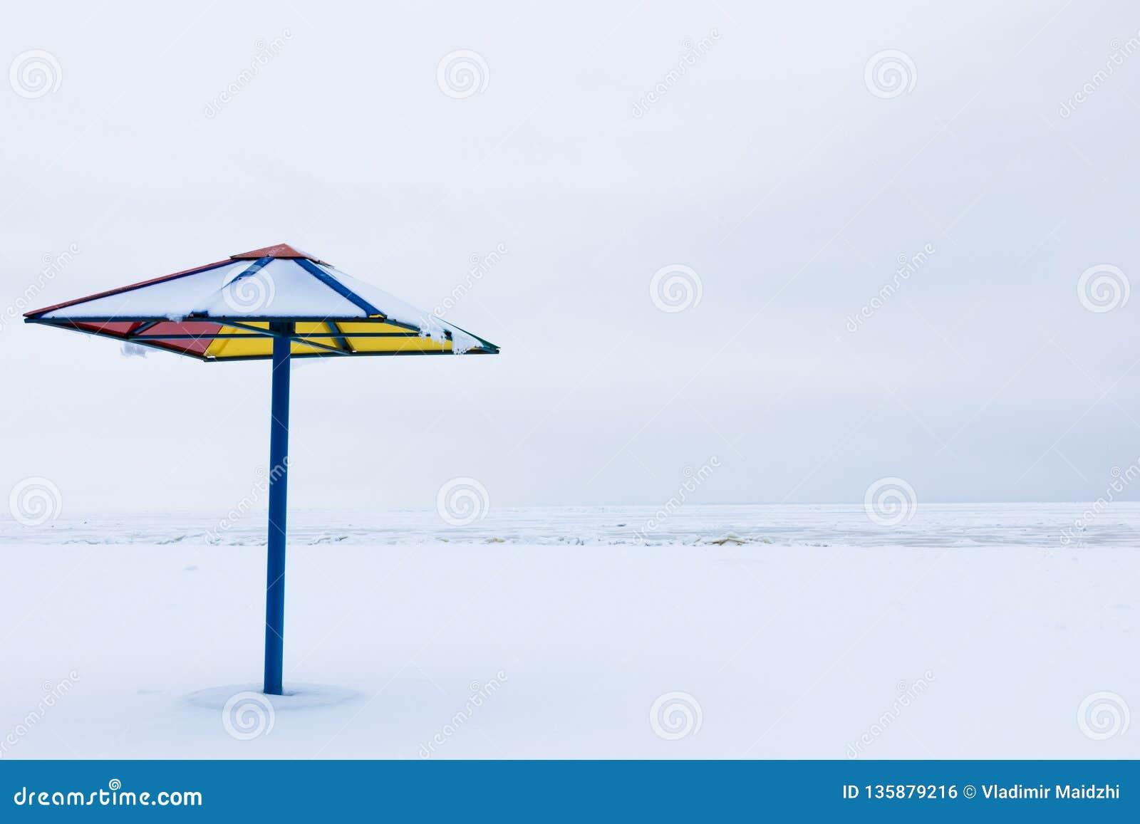 Apenas o para-sol ou o parasol na praia do inverno sob a neve