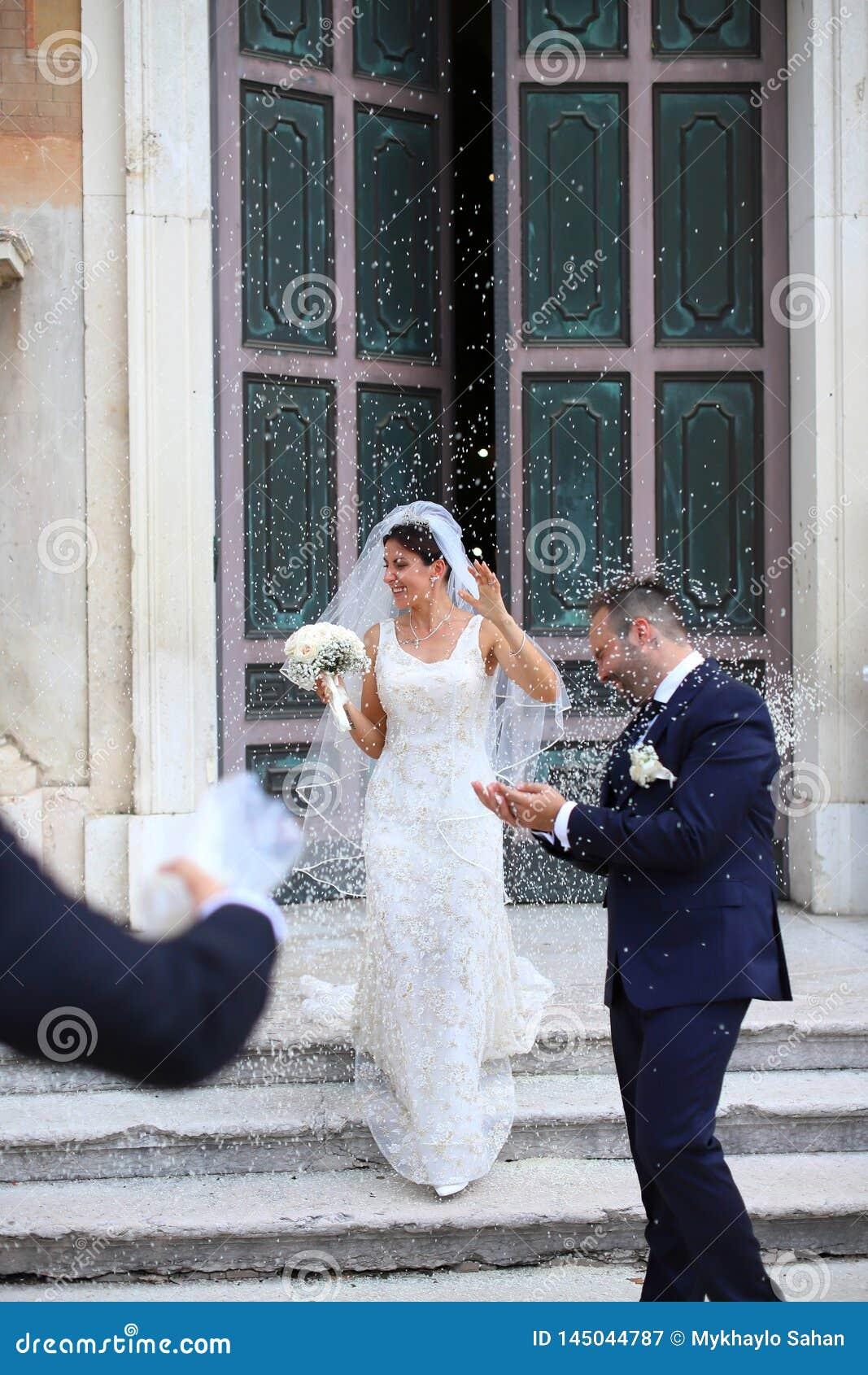 Apenas pareja casada feliz debajo de una lluvia del arroz