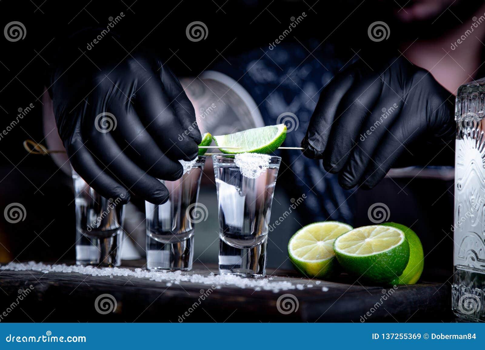 Aperitif med vänner i stången, tre exponeringsglas av alkohol med limefrukt och att salta för garnering Tequilaskott som är selek