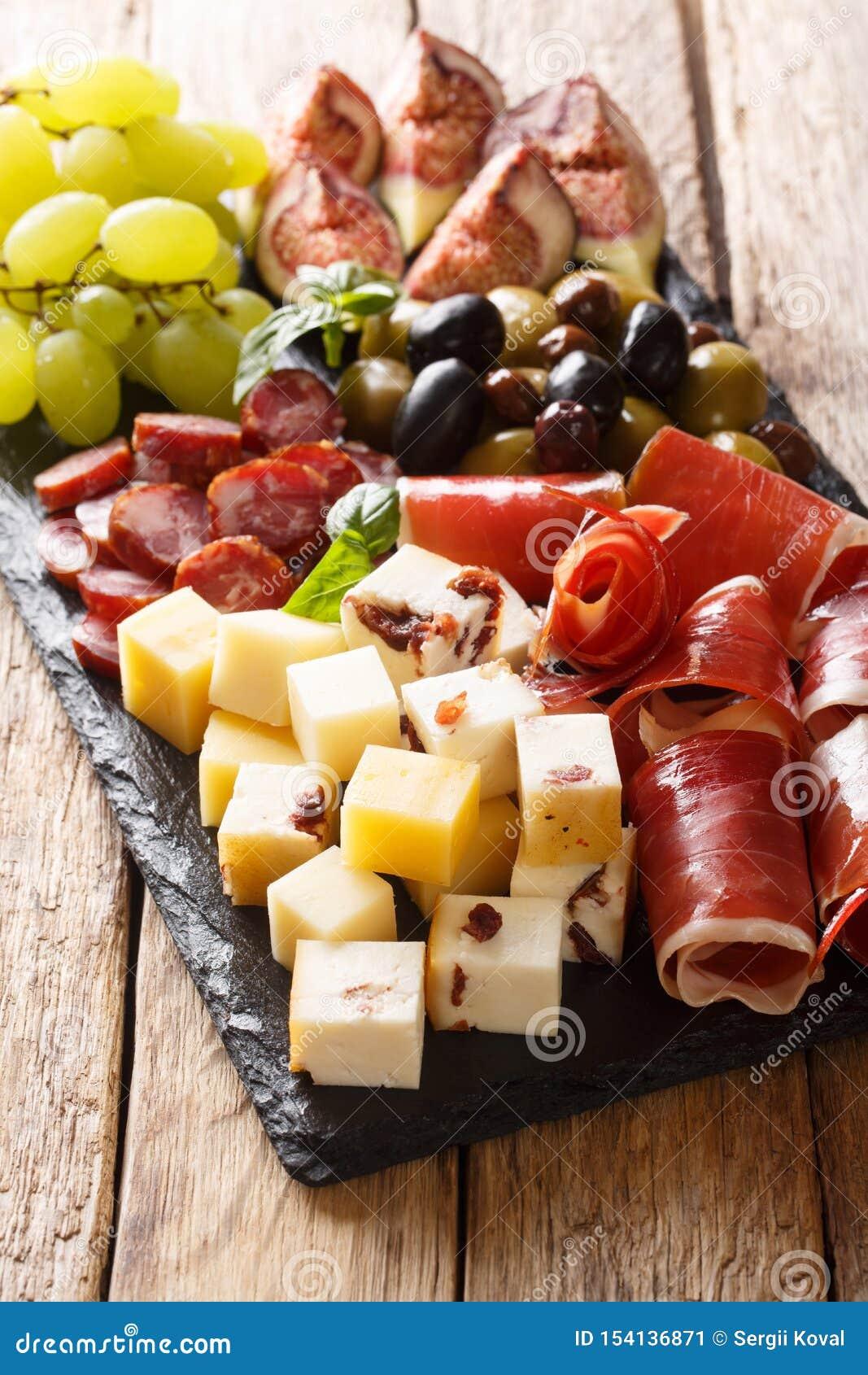 Aperitivo delicioso de antipasti del queso, del jamón de prosciutto, de las uvas, de los higos, de las salchichas y del primer de
