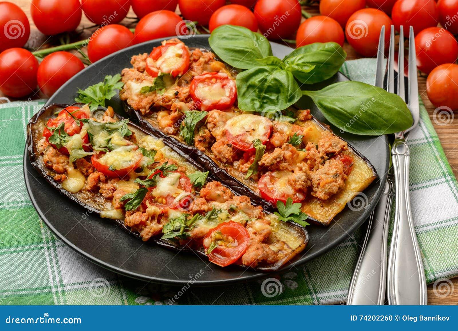 Aperitivo delicioso - las berenjenas asadas a la parrilla cocieron con la carne picadita, los tomates y el queso