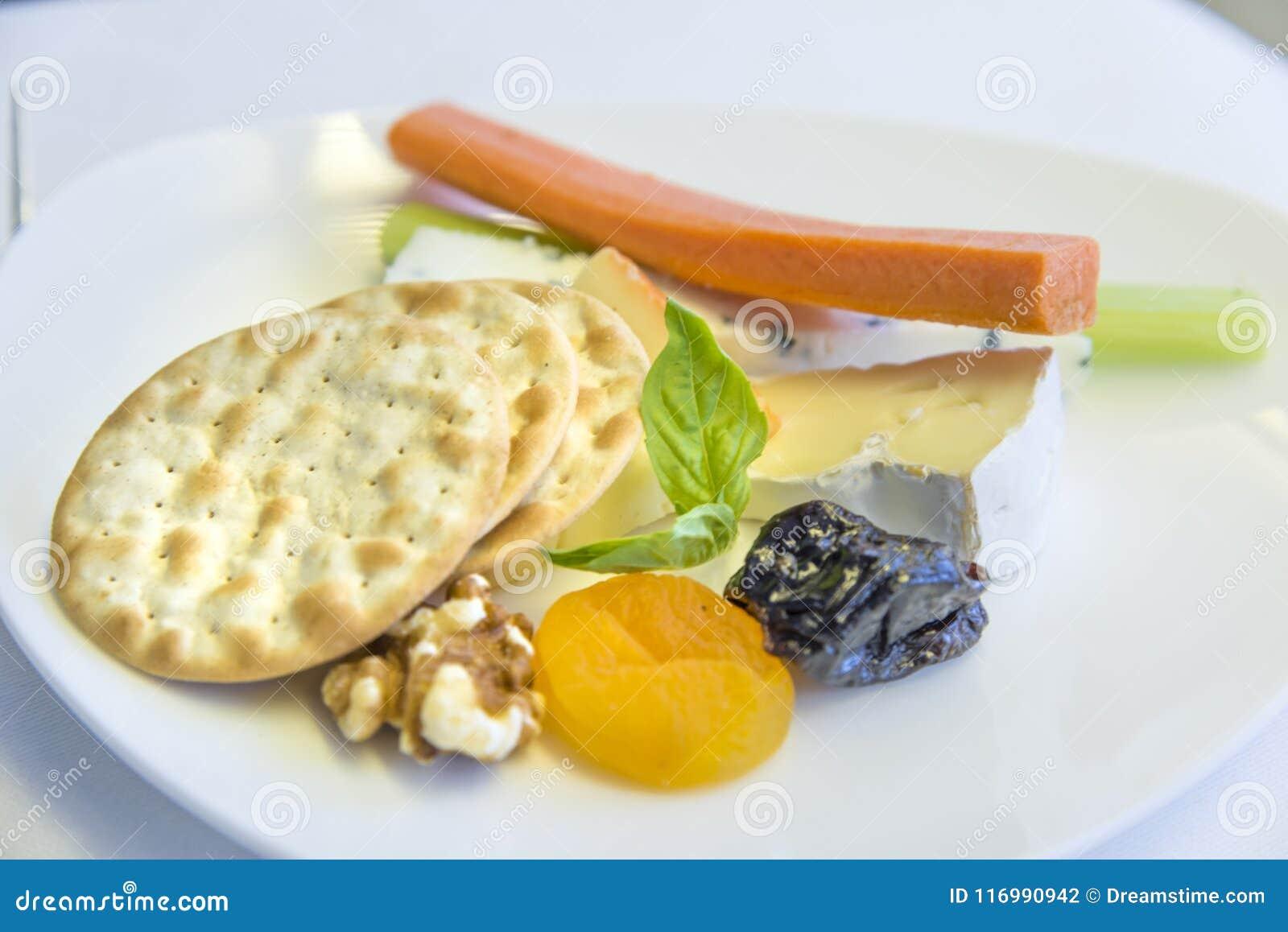 Aperitivo determinado de la comida de aviones en una bandeja, en una tabla blanca