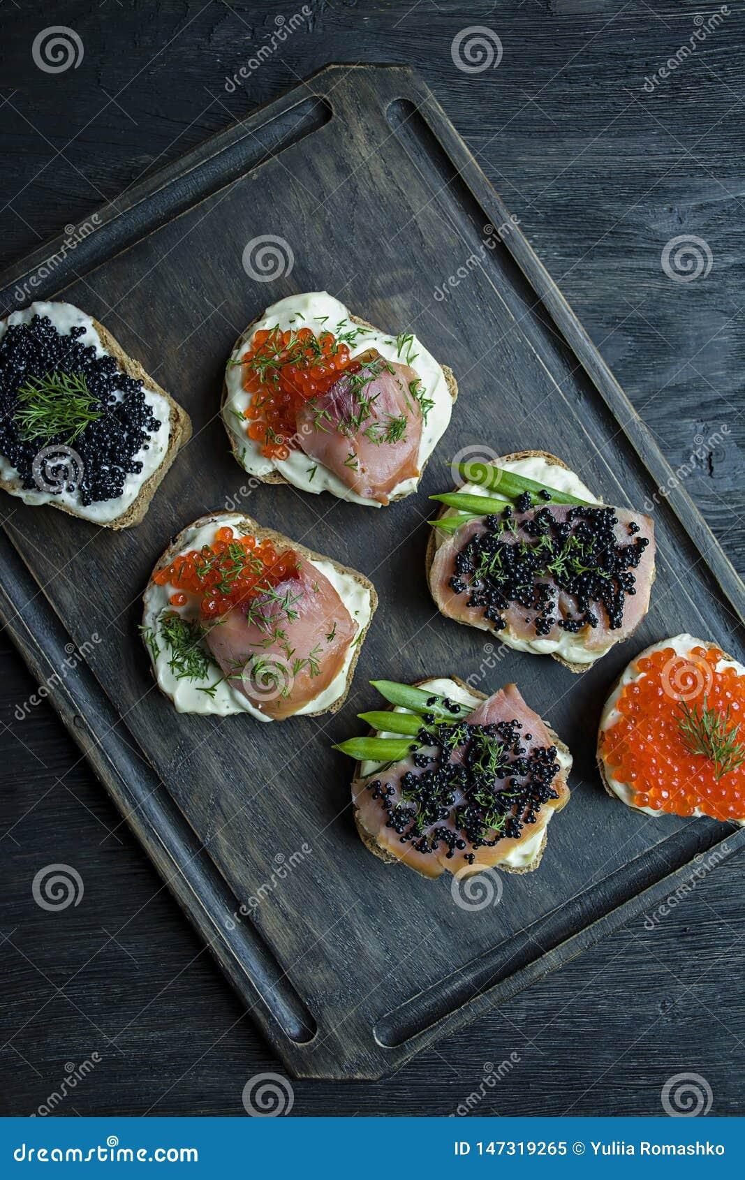Aperitivos con el caviar rojo y el caviar negro en una tajadera oscura Primer Fondo de madera oscuro