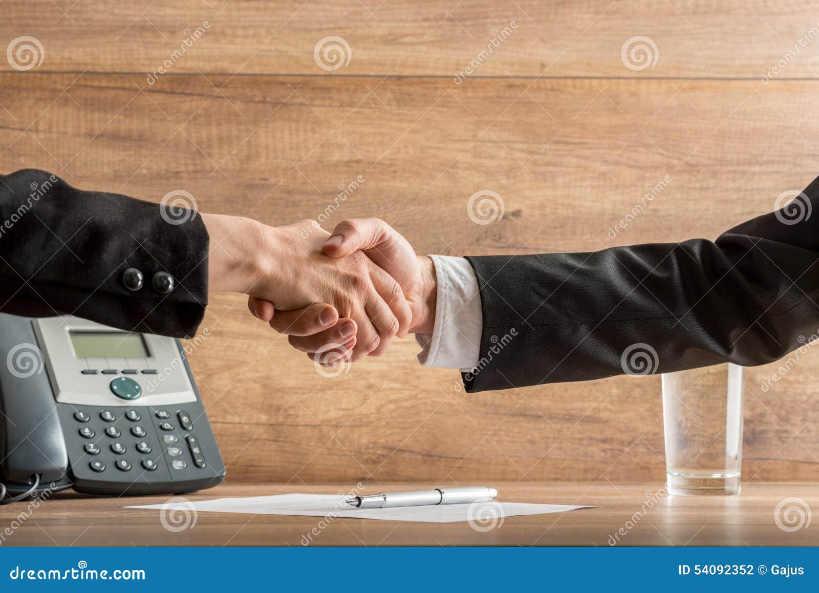 Aperto de mão dos sócios comerciais acima de um acordo escrito