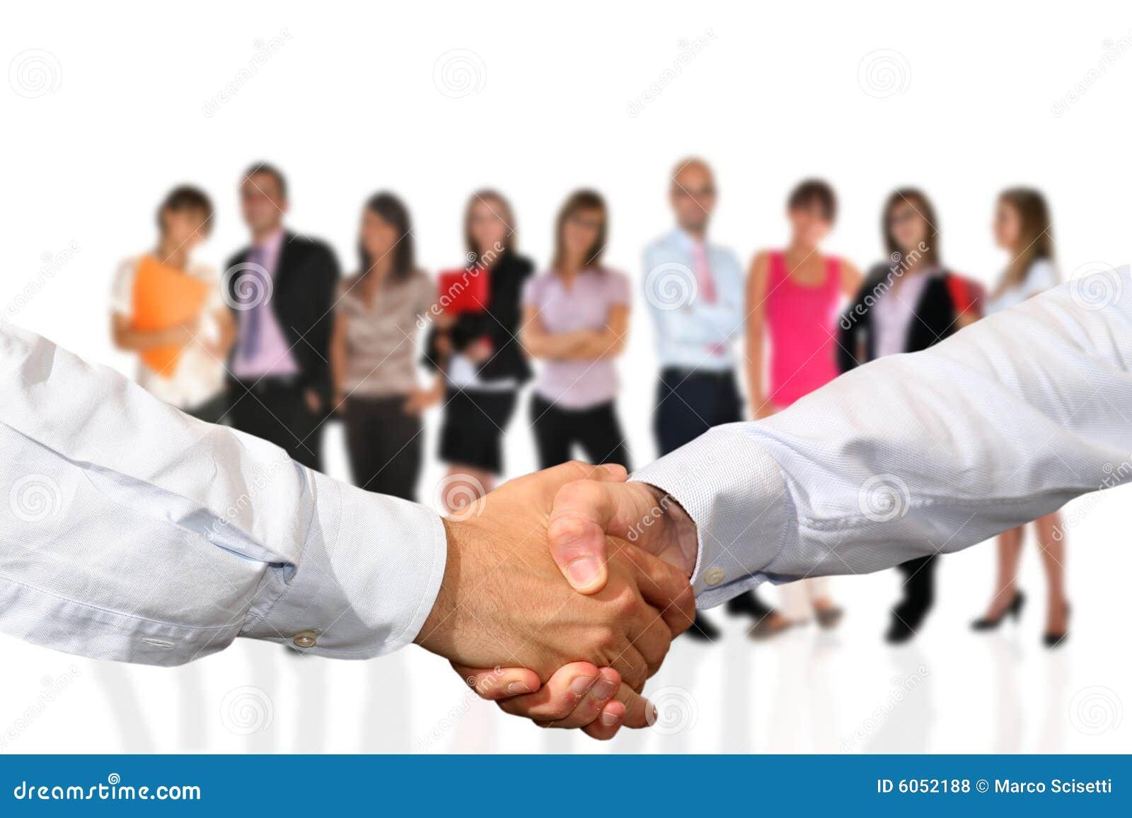 Aperto de mão e equipe do negócio