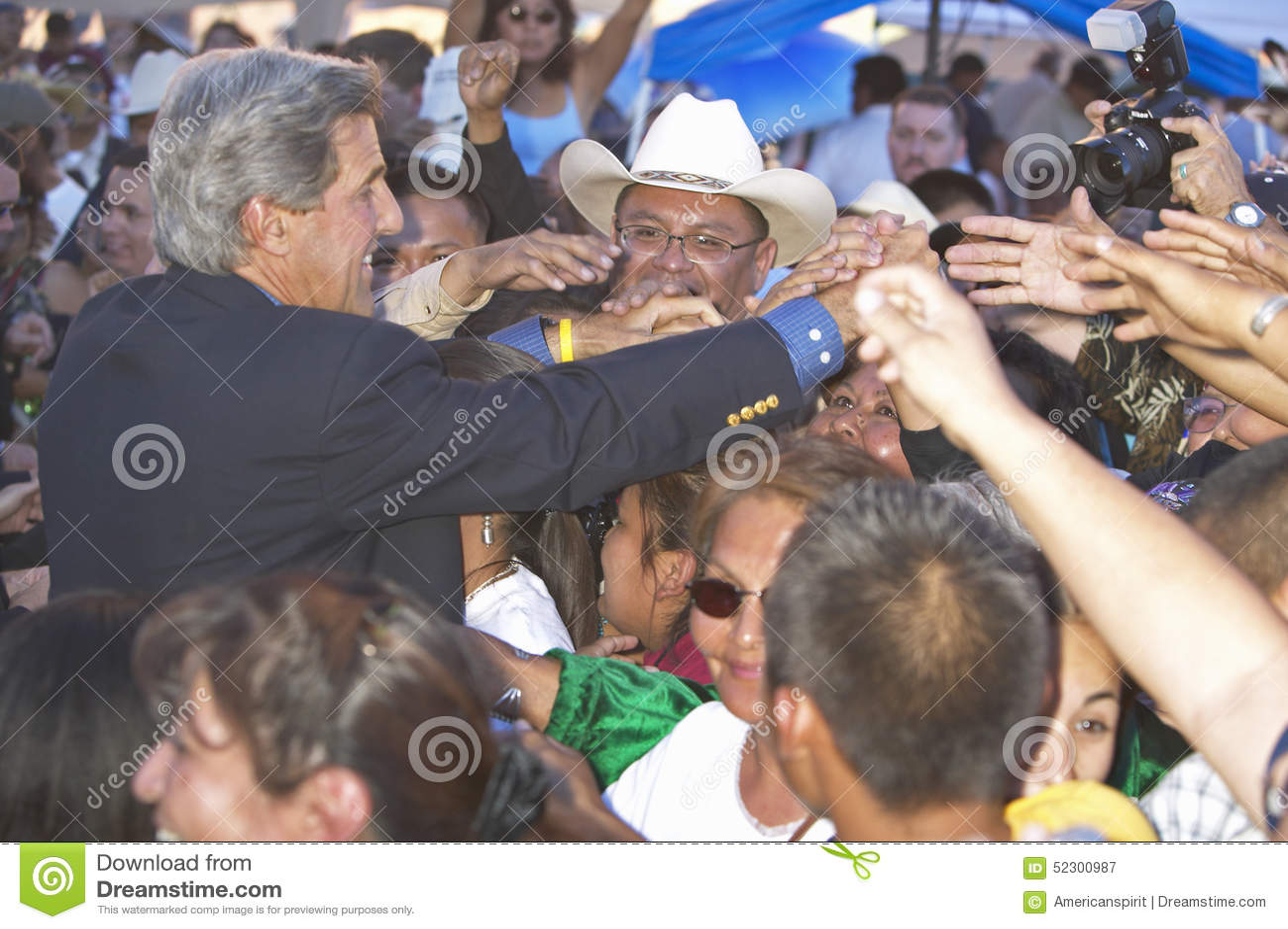 Apertos de mão do Senator John Kerry com membros da 83rd cerimónia indiana intertribal, Gallup da audiência, nanômetro