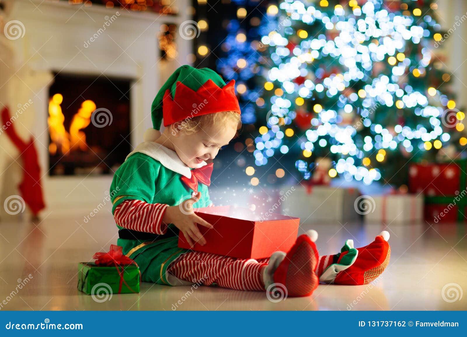 Apertura del niño presente en el árbol de navidad en casa Niño en traje del duende con los regalos y los juguetes de Navidad